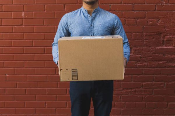 man holding shipping box on red brick600x400